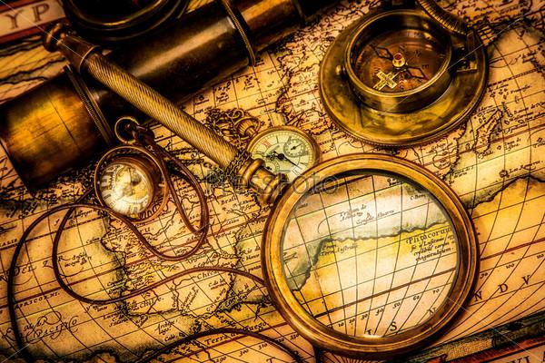 Старинное увеличительное стекло лежит на древней карте мира