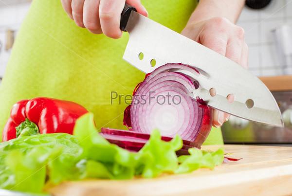 Женские руки режут луковицу
