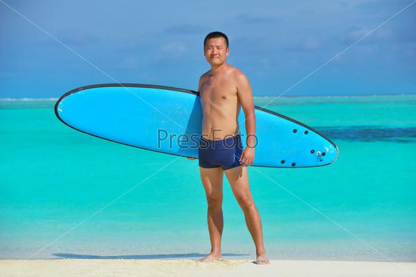 Мужчина с доской для серфинга на пляже