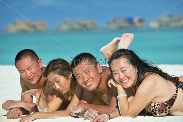 Фотография на тему Группа счастливых молодых людей веселится на пляже