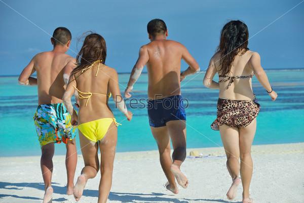 Группа счастливых молодых людей веселится на пляже