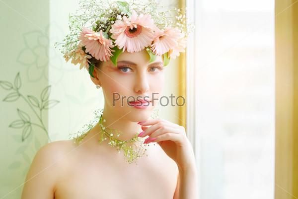 Красивая девушка в венке из цветов на светлом фоне