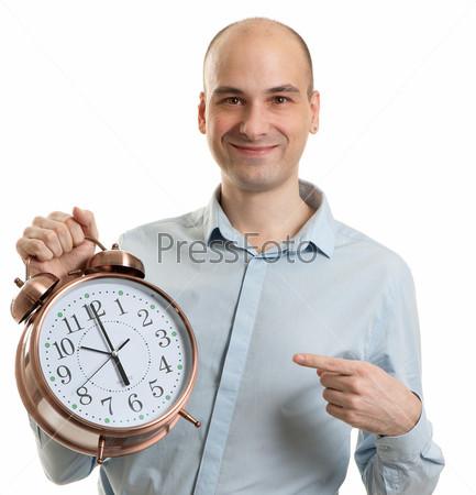 Улыбающийся мужчина показывает на большой будильник