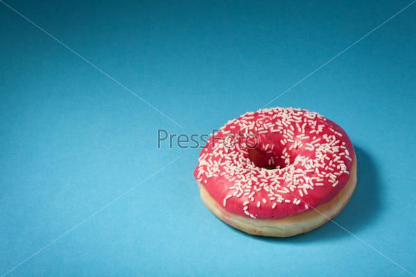 Пончик с красной глазурью, изолированный на синем фоне с местом для текста