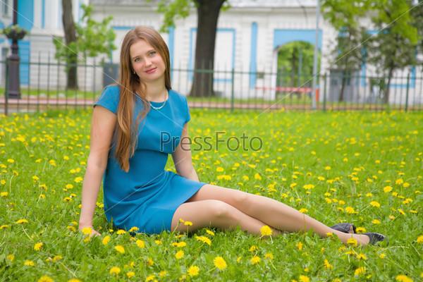 Фотография на тему Красивая молодая женщина сидит на весеннем лугу