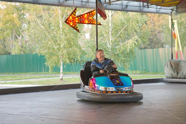 Пожилой мужчина в маленьком автомобиле в парке развлечений