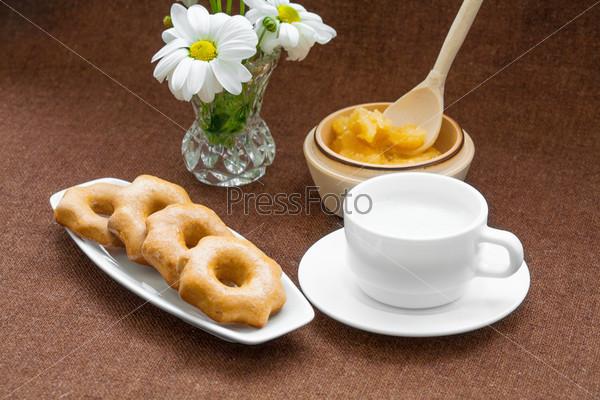Медовое печенье, чашка и вазы с ромашками