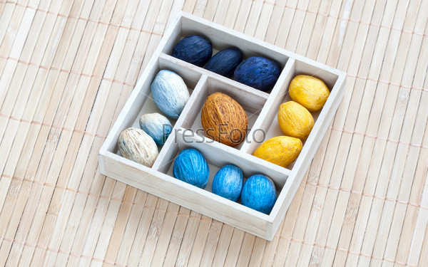 Коробка с цветными орехами на бамбуковой салфетке