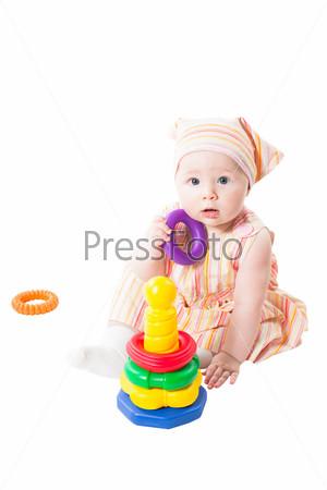 Девочка играет с игрушечной пирамидой, изолированная на белом фоне. Игрушка для детей