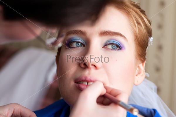 Визажист красит губы