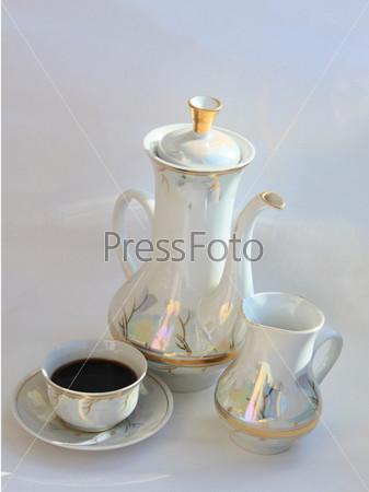 Маленький кувшин для сливок, кофейник и чашка кофе на сером фоне. Вертикальное фото