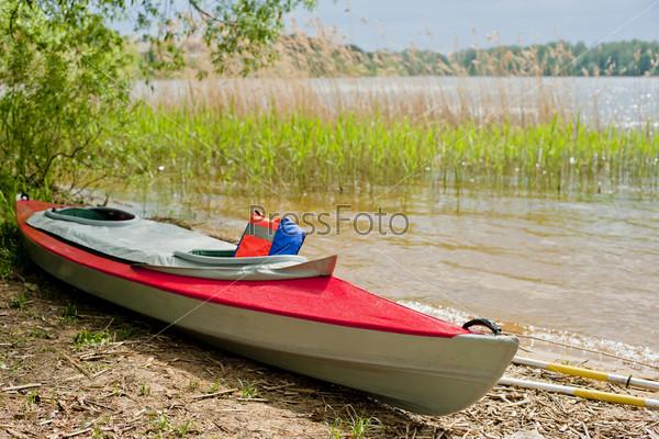 Складное красное каноэ на берегу озера