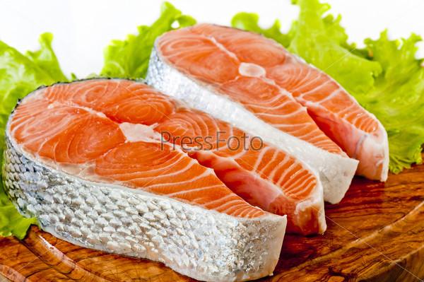 Свежий сырой лосось с листьями салата и лимоном