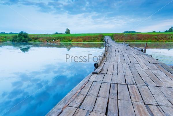 Фотография на тему Деревянный мост через небольшое озеро ранним утром