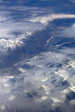 Снежный узор, облака и камни: вид с высоты