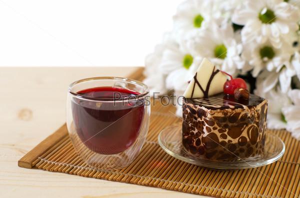 Чай, ромашки, миндальный пирог на деревянном столе