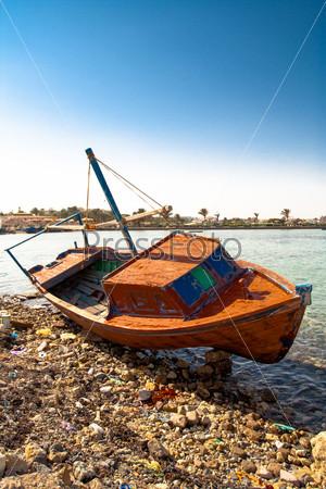 Красная лодка лежит на берегу