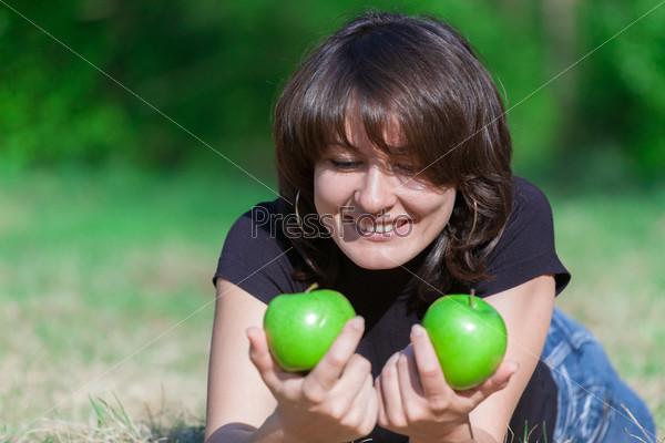 Хорошенькая молодая девушка и яблоки на сене