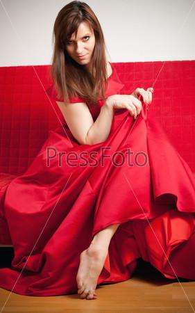 Фотография на тему Красивая женщина в красном бальном платье сидит на диване