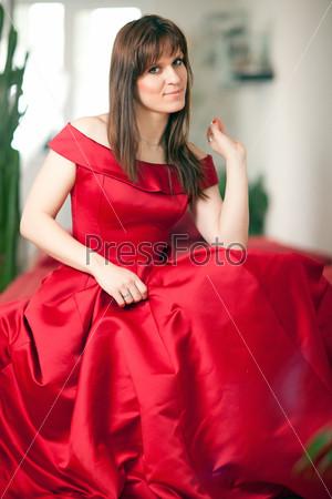 Красивая женщина в красном бальном платье сидит на диване