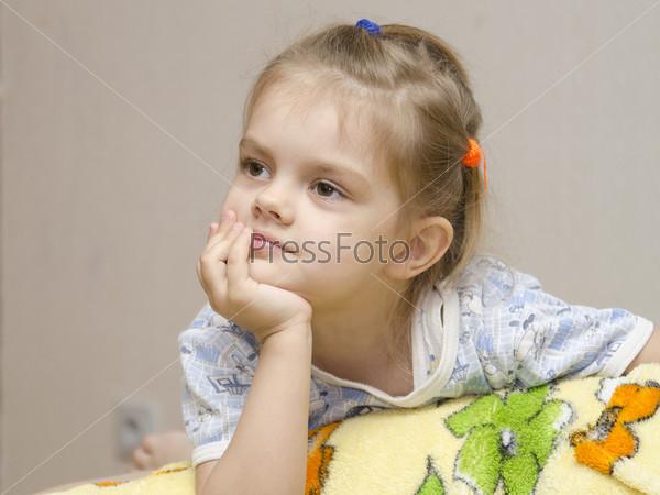 Четырехлетняя девочка увлеченно смотрит влево