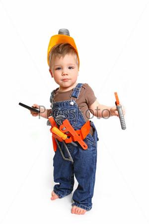 Маленький мальчик в оранжевом шлеме с инструментами и мобильным телефоном