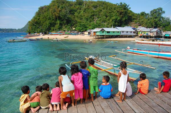 Дети на деревянном пирсе смотрят на море