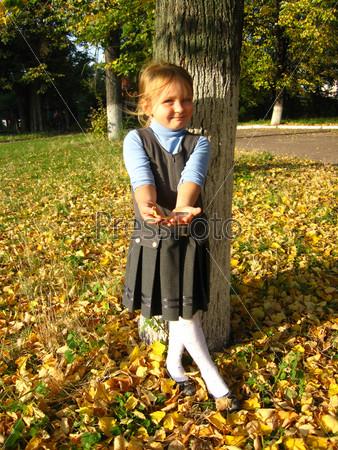Маленькая девочка с желтыми осенними листьями