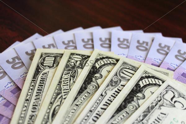 Доллары и гривны, изолированные на темном фоне