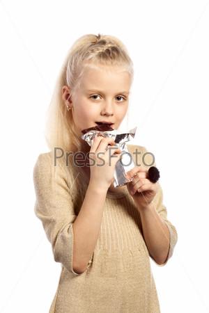 Красивая девочка кусает шоколад