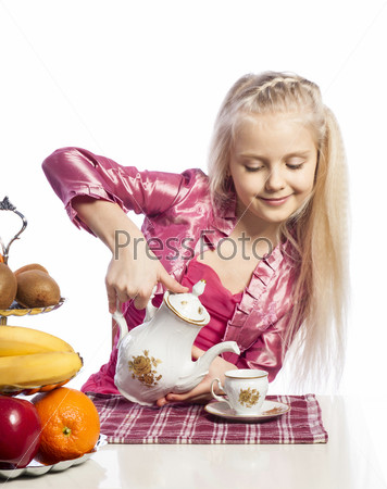 Красивая девочка наливает чай в чашку