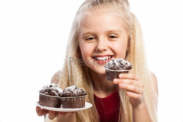Девочка смотрит на шоколадные кексы
