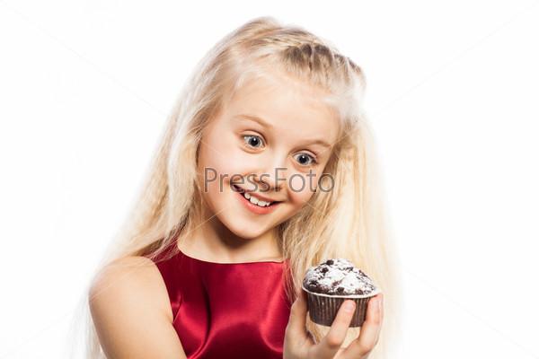 Фотография на тему Удивленная девочка смотрит на кекс