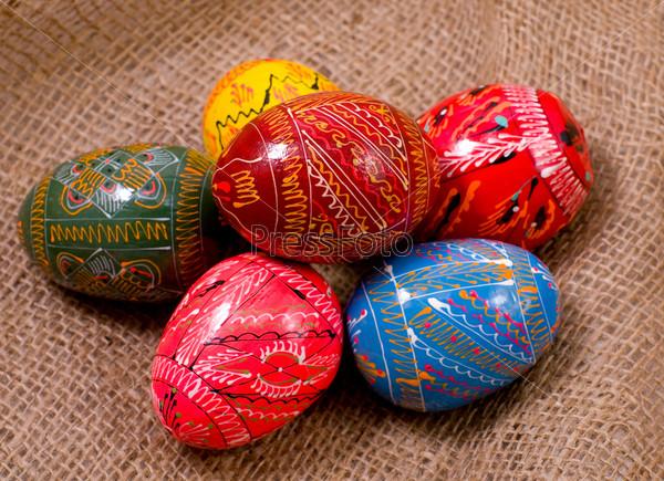 Красочные пасхальные яйца на фоне мешковины