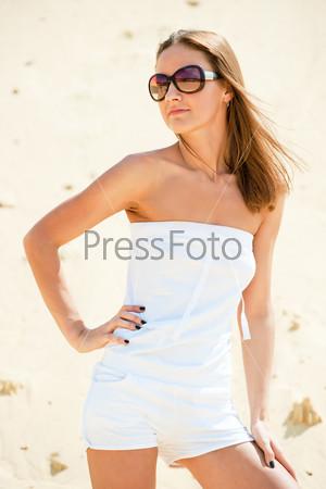 Фотография на тему Брюнетка в белом платье на фоне песка