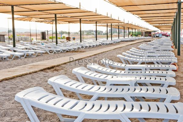 Пляжные стулья под навесом на песчаном пляже