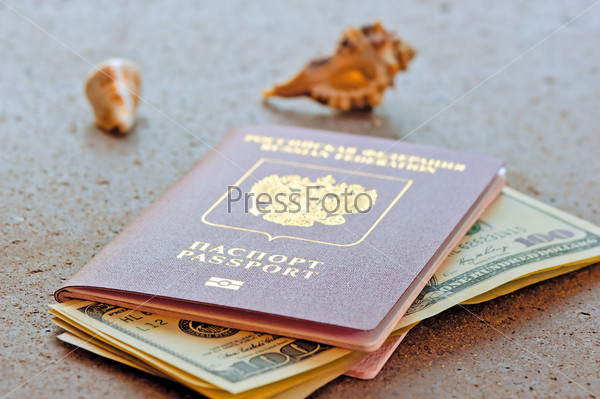 Российский паспорт с долларами и ракушки на гранитной столешнице