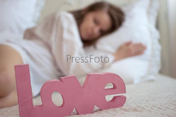 """Слово """"любовь"""" на кровати рядом с женскими ногами"""