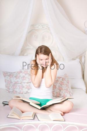 Испуганная девушка, читающая книгу на кровати