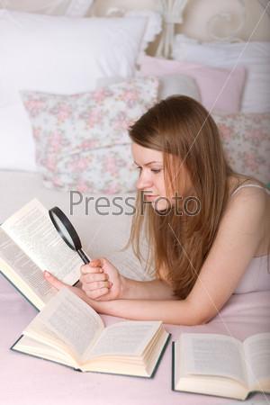Фотография на тему Молодая женщина читает книгу в постели