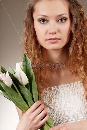 Женщина держит белые тюльпаны