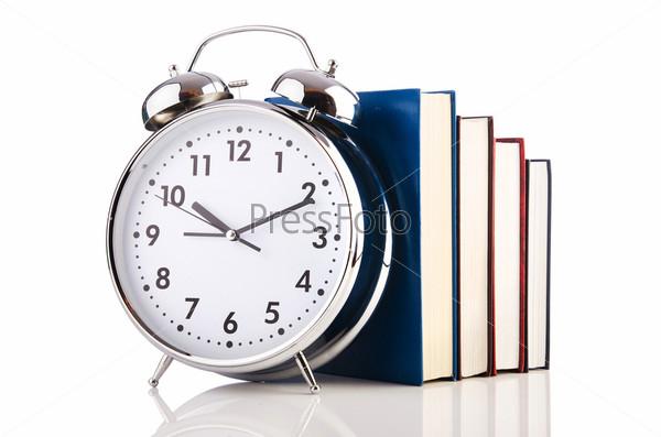 Фотография на тему Будильник и книги, изолированные на белом