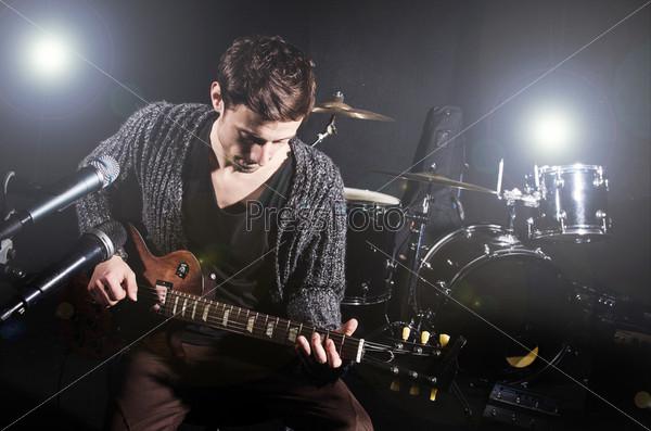 Мужчина играет на гитаре во время концерта