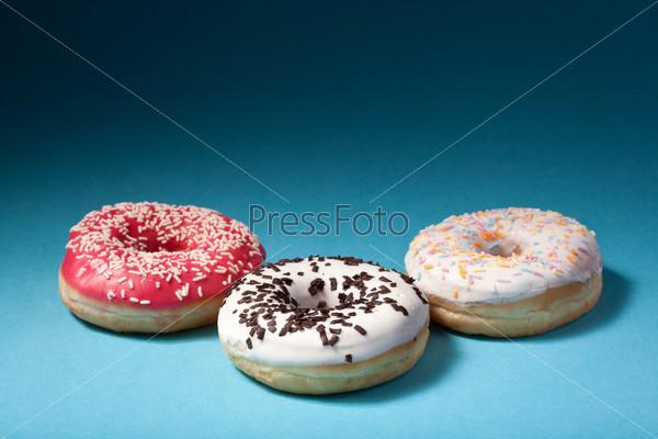 Три пончика с цветной глазурью на синем фоне