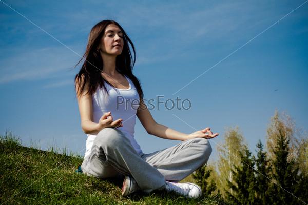 Фотография на тему Красивая молодая женщина медитирует на траве