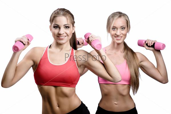 Две красивых молодых женщины делают фитнес-упражнения с гантелями