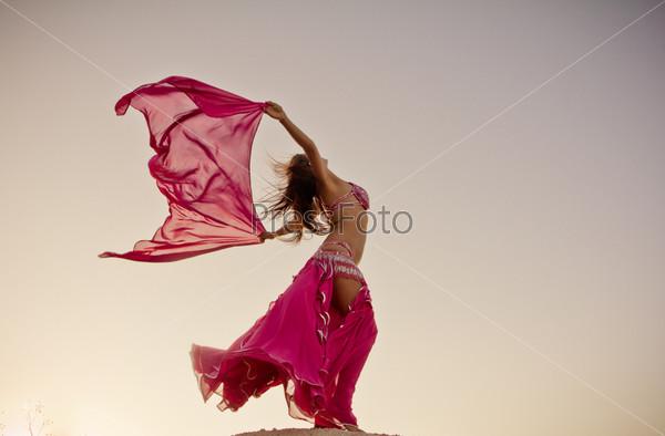 Красивая девушка держит розовую ткань на ветру на фоне неба