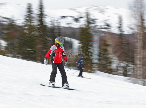 Ребенок едет вниз по склону на сноуборде, Шерегеш, Россия
