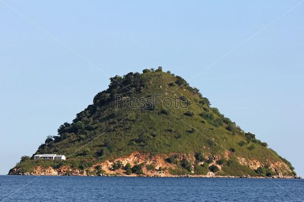 Одинокий пирамидальный остров в море с белым домом, Индонезия