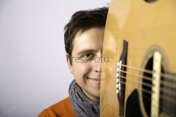 Фотография на тему Счастливый мужчина смотрит из акустической гитары